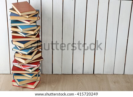 High stack of books on white wooden wall background - stock photo