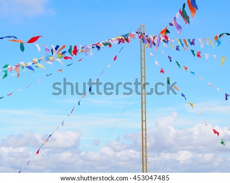 high tall pole with colorful triangle flags hanging on ropes outdoor with bright blue sky white clouds background as sign symbol for festival fun events or carrousel
