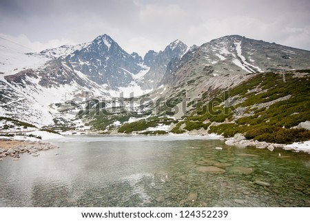 High Tatras with snowy peaks and lake - stock photo