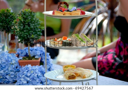 High Tea, display of a selection of petit-fours, canapes, savories and sandwiches at a formal luncheon english tea party - stock photo