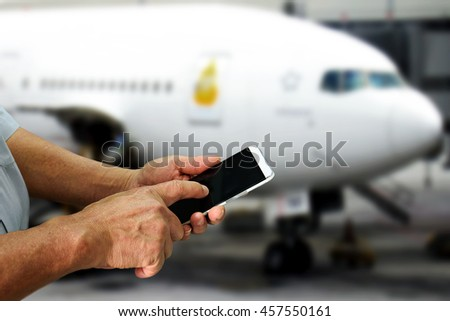High tech old man hands use smartphone , elder lifestyle , Mobile Boarding Passes concept with airplane abstract background , copyspace area