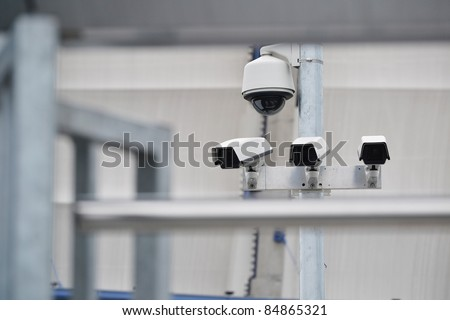 High tech overhead security camera system installed in guarded industrial area - stock photo