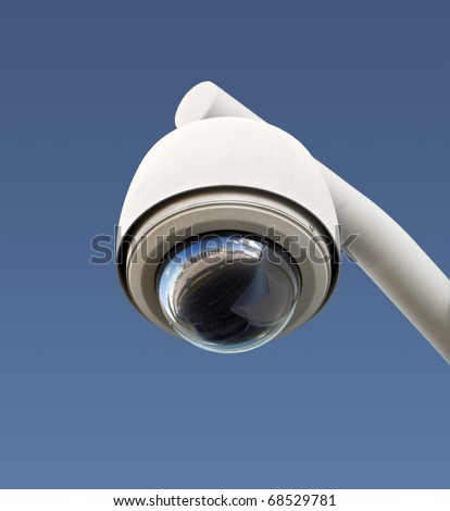 High tech overhead security camera with a gradient blue sky.