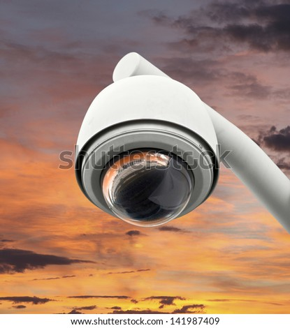 High tech overhead security camera with bright sunset sky. - stock photo