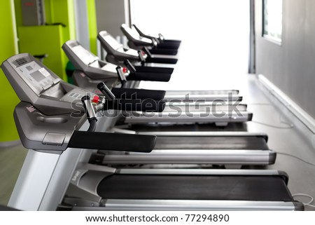 High technology motorized Treadmills in a row (using shallow depth of field) - stock photo