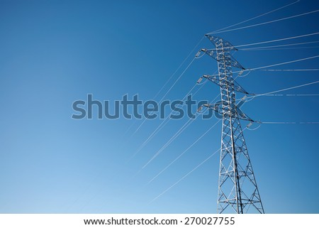 High tension electrical power lines and pylon tower against sky. Modern industrial energy line.
