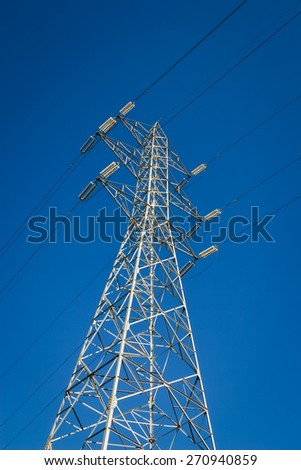 High tension electrical power lines and pylon tower against sky. Modern industrial energy line. - stock photo