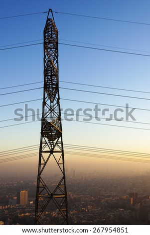 High tension electrical tower side faced, background Barcelona city under pollution smog.