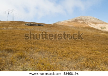 High tension power lines ascending a hill, Los Osos, California - stock photo