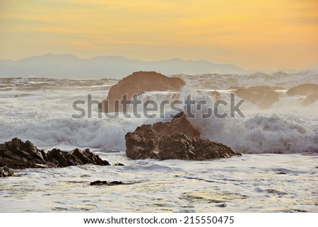 High tide at sunset crashing on shore line rocks near Botanical Beach, Port Renfrew, Vancouver Island, British Columbia in the Strait of Juan de Fuca, Pacific Ocean, across from the Olympic Mountains. - stock photo
