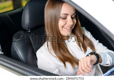 High time. Young beautiful woman sitting in new car and checking time.