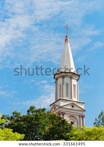 High tower turret of the church in green trees under blue sky - stock photo