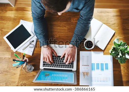 High view of man working on laptop at office desk, business success concept - stock photo