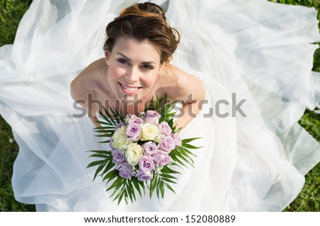 High View Portrait Of Beautiful Happy Bride Sitting On The Grass - stock photo