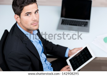 High view portrait young businessman using digital tablet at desk in office - stock photo