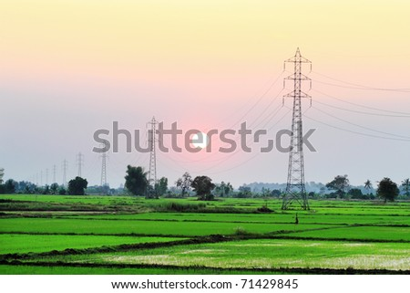 high voltage cable , tower on sunset , green view - stock photo