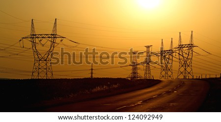 high voltage electric towers during sunset