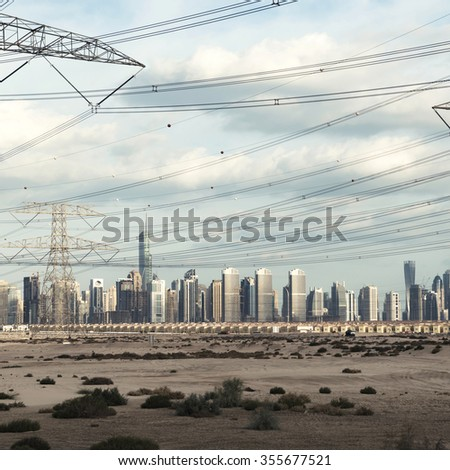 High voltage electrical lines passing by a massive skyline in Dubai. - stock photo