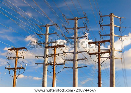 High voltage electrical transmission power lines against late afternoon sky. - stock photo