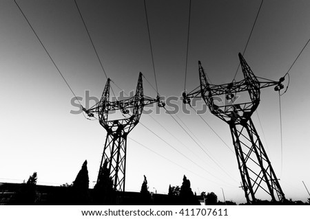 High voltage electrical transmission towers electricity pylons and power lines black silhouette on field, black and white image - stock photo