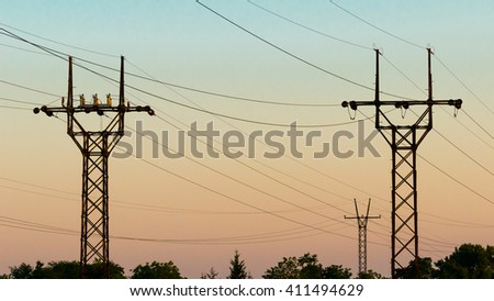 High voltage electrical transmission towers electricity pylons and power lines black silhouettes on the sky at sunset  - stock photo