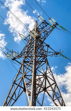 High voltage electricity pylon against blue sky - stock photo