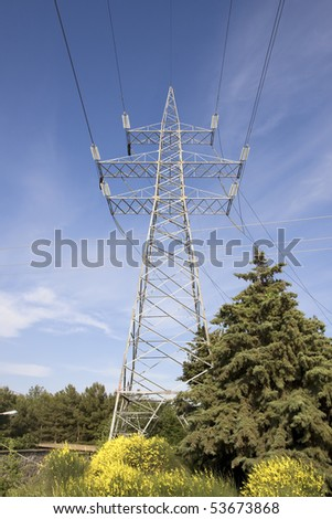 High voltage electricity pylon against blue sky - stock photo