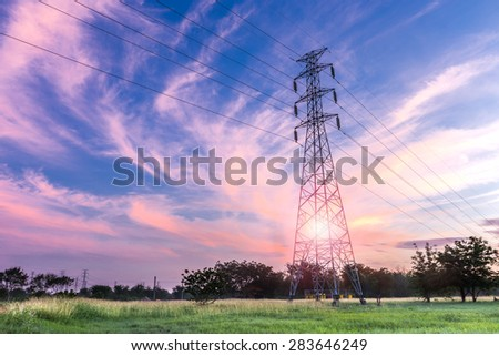 High voltage electricity pylon on sunrise background - stock photo