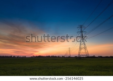 High voltage electricity pylon sunset - stock photo