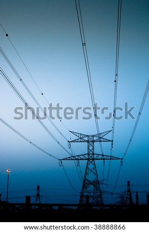 high voltage electricity pylons near dusk - stock photo