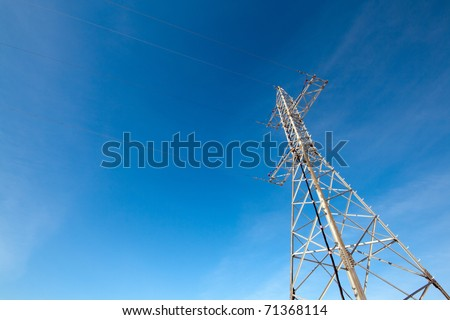 High voltage electricity tower against blue sky - stock photo