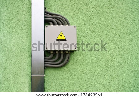 High voltage junction box with cables by the cable tray on the green wall - stock photo