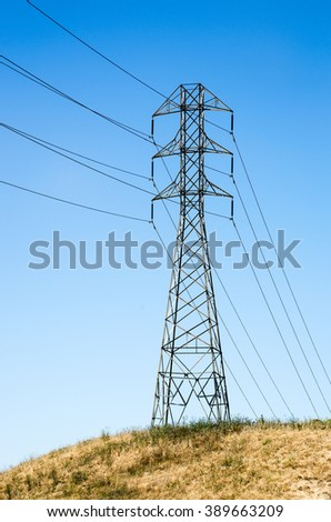 High voltage line among yellow grass beneath clear sky - stock photo