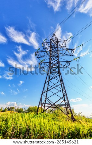High voltage line beneath the blue cloudy sky