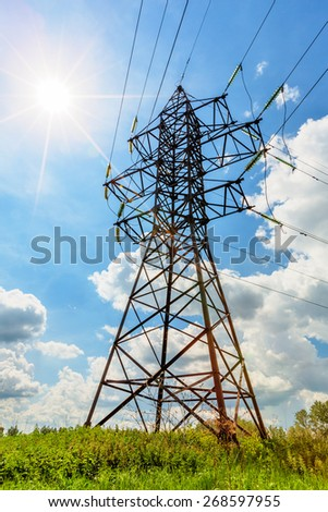 High voltage line beneath the sun and blue cloudy sky - stock photo