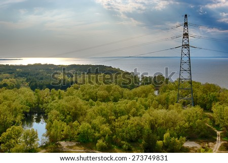 high-voltage line in a forest at sunset - stock photo