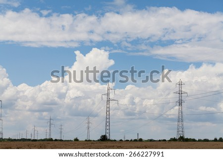 High voltage lines and power pylons in a agricultural landscape on a sunny day with cirrus clouds in the blue sky.