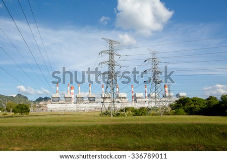 High voltage lines and power pylons in a flat and green agricultural landscape with cirrus clouds on blue sky, Mea Moh, Lampang, Thailand.