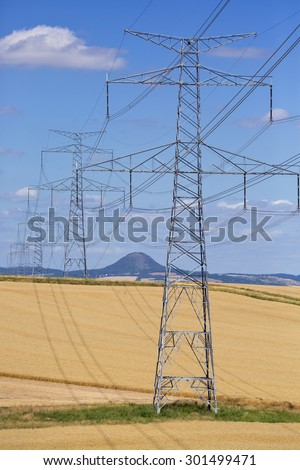 High voltage lines and power pylons in a green agricultural landscape on a sunny day with cirrus clouds in the blue sky. - stock photo