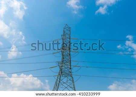 High voltage lines and power pylons with cirrus clouds in the blue sky