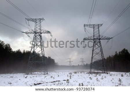 High voltage lines in foggy winter day - stock photo