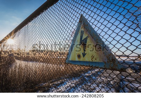 High voltage old sign on the fence the sun shines through the fence, focus on sign - stock photo