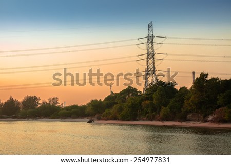 High voltage pole over coastal forest - stock photo