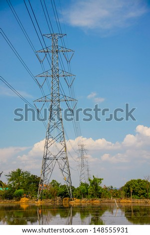 High voltage pole with blue sky and cloud on bright day - stock photo