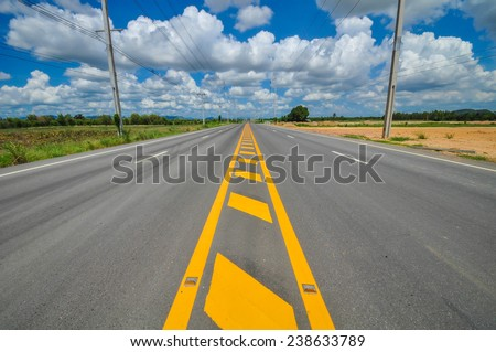 High voltage poles and yellow line on the road,Hua Hin road Thailand. - stock photo