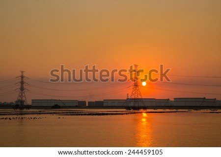 High voltage post and industry zone offshore before sunset - stock photo