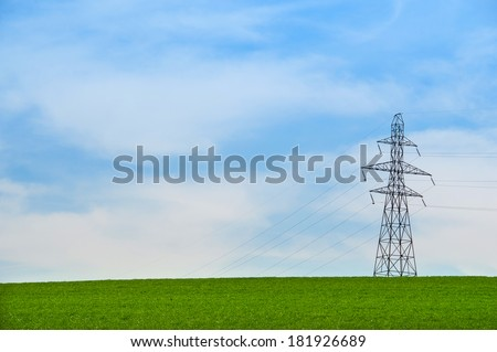 high voltage post. High-voltage tower on green field and blue sky - stock photo