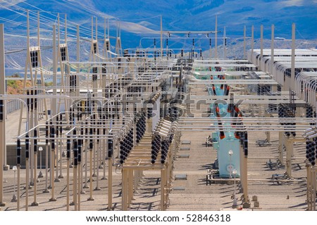 High voltage power distribution substation overlooking river canyon - stock photo