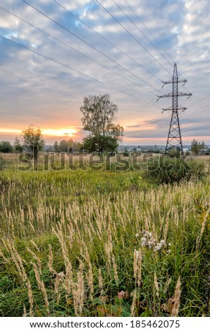 High voltage power line in meadow over sunset sky - stock photo