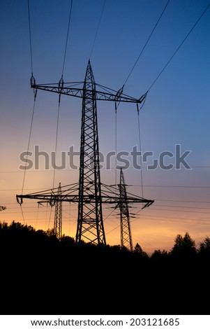 high voltage power line in the sundown - stock photo